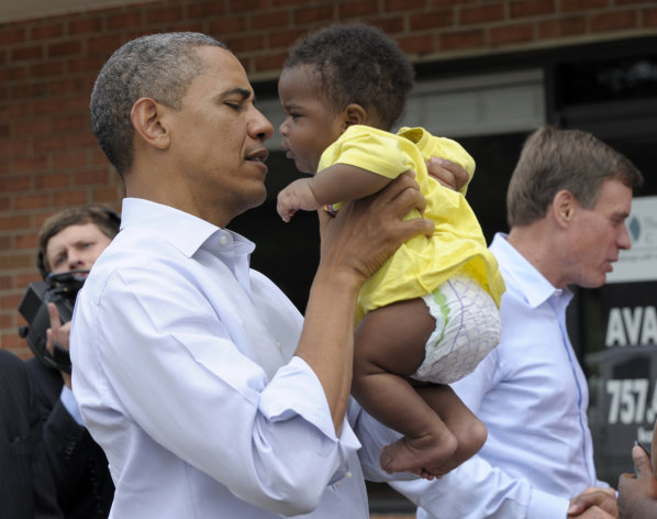 President Barack Obama picks up Kerry Christophe III during a stop at Rick&#39;s Cafe in Virginia Beach, Va., Friday, July 13, 2012. Obama is spending the day in Virginia campaigning. Sen. Mark Warner, D-Va., is at right. (AP Photo/Susan Walsh)