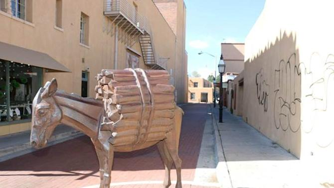 "This undated photo provided by the city of Santa Fe, N.M., shows ""Homage to the Burro,"" sculpture by artist Charles Southard in Santa Fe, N.M. The City of Santa Fe Arts Commission is working with artist Taylor Mott to reconstruct and replace the tail on the sculpture. Last week officials noticed that someone broke the tail off of the sculpture and vandals also tagged the wall on a building nearby. Mott is moving forward with fabricating a replacement tail for the artist's review and approval. When approved, the tail will be welded in place. (AP Photo/The city of Santa Fe)"