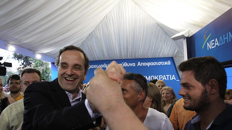 Greek conservative leader Antonis Samaras of New Democracy visits an elections kiosk in Syntagma square in central Athens, Monday, June 11, 2012. Greeks go to the polls again on Sunday, June 17. (AP Photo/Petros Karadjias)