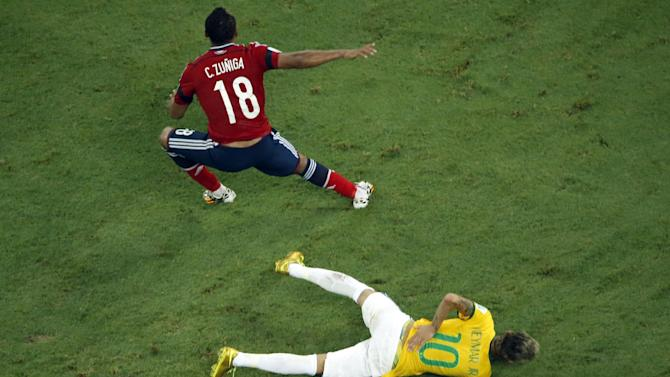 Brazil's Neymar holds his back after a hefty challenge from Colombia's Juan Zuniga during the World Cup quarter-final match at the Castelao Stadium in Fortaleza, on July 4, 2014