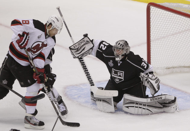 Los Angeles Kings goalie Jonathan Quick (32) deflects a shot attempt as New Jersey Devils right wing Dainius Zubrus (8) looks for the rebound in the first period during Game 3 of the Stanley Cup Final