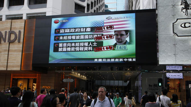 A TV screen shows a news report of Edward Snowden, a former CIA employee who leaked top-secret documents about sweeping U.S. surveillance programs, at a shopping mall in Hong Kong Saturday, June 22, 2013. Hong Kong was silent Saturday on whether the former National Security Agency contractor should be extradited to the United States now that he has been charged with espionage, but some legislators said the decision should be up to the Chinese government. (AP Photo/Kin Cheung)