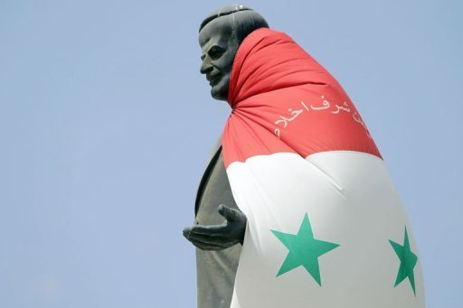 A national flag hangs on a statue of Syria's late president Hafez al-Assad
