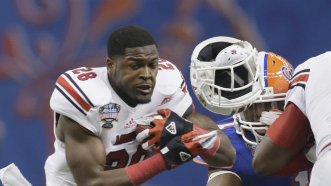 Louisville running back Jeremy Wright (28) has his helmet knocked off by Florida linebacker Jon Bostic (1) as Florida defensive lineman Dominique Easley (2) pursues in the first quarter of the Sugar Bowl NCAA college football game Wednesday, Jan. 2, 2013, in New Orleans. (AP Photo/Dave Martin)