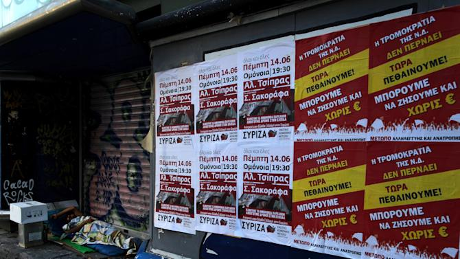 """A homeless man sleeps next  election posters, with far left political party, on right, reading """"we are dying now, we can live without Euro"""", in central Athens, on Saturday, June 16, 2012.  Greeks cast their ballots this Sunday for the second time in six weeks, after May 6 elections left no party with enough seats in Parliament to form a government and coalition talks collapsed.(AP Photo/Petros Giannakouris)"""