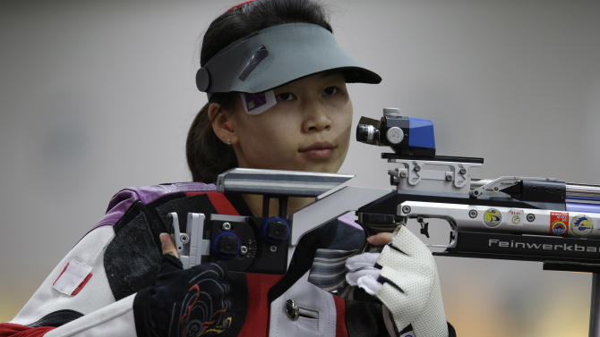 China's Yi Siling shoots during qualifiers for the women's 10-meter air rifle event, at the 2012 Summer Olympics, Saturday, July 28, 2012, in London. (AP Photo/Rebecca Blackwell)