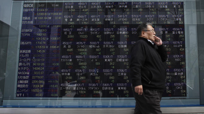 A man talking on a mobile phone walks past an electronic board showing stock prices outside a securities company in Tokyo Thursday, March 7, 2013. Japan's Nikkei 225 index topped 12,000 for the first time in more than four years, but stock markets elsewhere in Asia flagged following Wall Street's eye-popping performance this week. (AP Photo/Shuji Kajiyama)