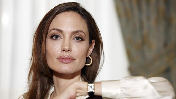 """FILE-  In this Saturday, Dec. 3, 2011 file photo, actress Angelina Jolie poses for a portrait to promote her directorial debut of the film """"In the Land of Blood and Honey""""  in New York. Jolie authored an op-ed for Tuesday's May 14, 2013 New York Times where she writes that in April she finished three months of surgical procedures to remove both breasts as a preventive measure. She says she's kept the process private but is writing about it now with hopes she can help other women. (AP Photo/Carlo Allegri, File) ITALY OUT"""