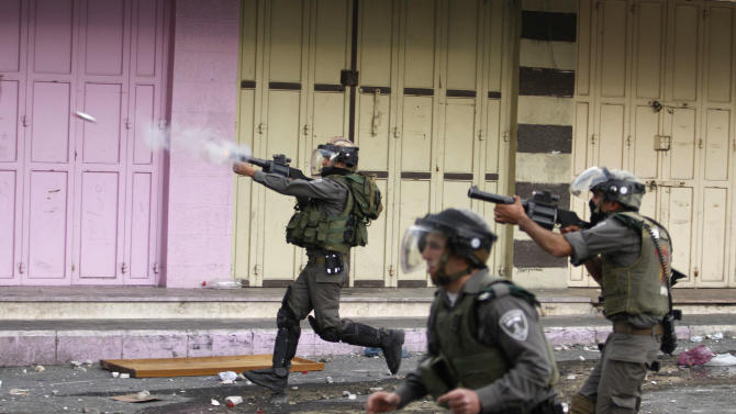 Israeli border policemen fire tear gas during clashes after the funeral of Arafat Jaradat in the West Bank of Hebron, Monday, Feb. 25, 2013. Thousands have attended the funeral procession of a 30-year-old Palestinian man who died under disputed circumstances in Israeli custody. Palestinian officials say autopsy results show Jaradat was tortured by Israeli interrogators, while Israeli officials say there's no conclusive cause of death yet and that more tests are needed.(AP Photo/Nasser Shiyoukhi)