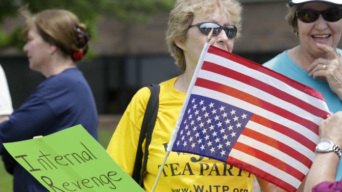 A woman holds an upside-down flag during a tea party rally protesting extra IRS scrutiny of their groups, Tuesday, May 21, 2013, in Cherry Hill, N.J. Tea party activists waving flags and signs, singing patriotic songs and chanting anti-IRS slogans protested outside federal buildings across the country to protest the agency's extra scrutiny of conservative groups. (AP Photo/Mel Evans)