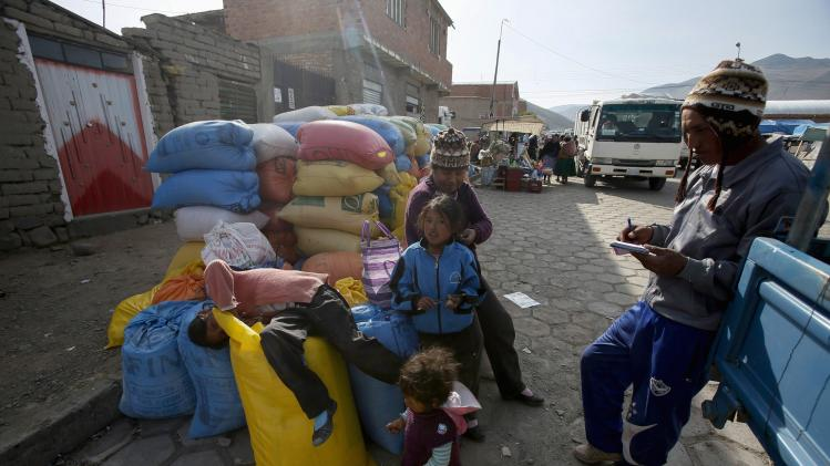 A quinoa grower and his family are seen with their bags of quinoa at a marketplace for small and medium-sized quinoa growers in Challapata, south of La Paz