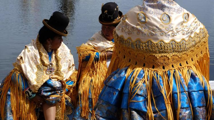 Women participating in Morenada dance rest during celebrations at the Festival for Apostle Santiago in Guaqui