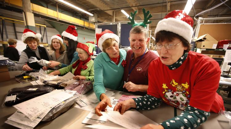 LL Bean employees wear Santa Claus hats and antlers as they celebrate the holiday spirit while working in the company's order fulfillment center, Thursday, Dec. 20, 2012, in Freeport, Maine. The outdoors store is making its final push to get things shipped in time for Christmas. (AP Photo/Robert F. Bukaty)