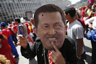 A supporter of Venezuela&#39;s President Hugo Chavez wears a mask depicting him during a rally in Caracas February 27, 2013. REUTERS/Jorgre Silva