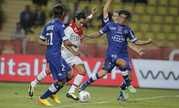 Monaco's Falcao of Colombia, center, Bastia's Fethi Harek of Algeria, left and Bastia's Francois J Modesto of France challenges for the ball during their French League One soccer match, in Monaco stad