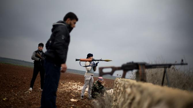 Free Syrian Army fighters take their positions, close to a military base, near Azaz, Syria, Monday, Dec. 10, 2012. The gains by rebel forces came as the European Union denounced the Syrian conflict, which activists say has killed more than 40,000 people. (AP Photo/Manu Brabo)