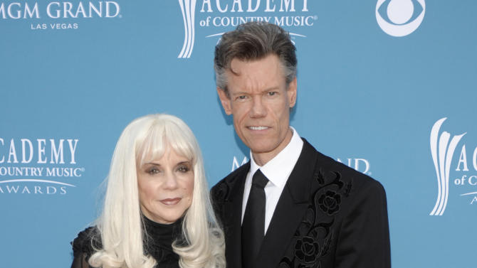 FILE - In this April 18, 2010 file photo, country singer Randy Travis, right, and then wife Elizabeth arrive at the 45th Annual Academy of Country Music Awards in Las Vegas. Travis has filed a countersuit against his ex-wife claiming she's been divulging confidential information about the country music singer that was calculated to damage his reputation and career. The court documents filed recently in a federal court in Nashville don't say what information Elizabeth Travis is alleged to have revealed. The filings are the latest salvo in the feud between the Travises. The couple divorced in 2010 after 19 years of marriage. Elizabeth Travis had been his manager for more than three decades. She sued him last month claiming that Randy Travis made it impossible for her to do her job and terminated her management contract without proper written notice. (AP Photo/Dan Steinberg, file)