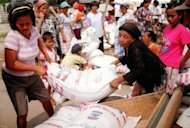This file photo shows Indonesian women moving sacks of rice for distribution in a charity event organized by aid agency World Vision in a slum area in North Jakarta. Australia's plan to scale back foreign aid growth to help produce a budget surplus was criticised by charity groups on Wednesday, with World Vision saying it could cost up to 200,000 lives
