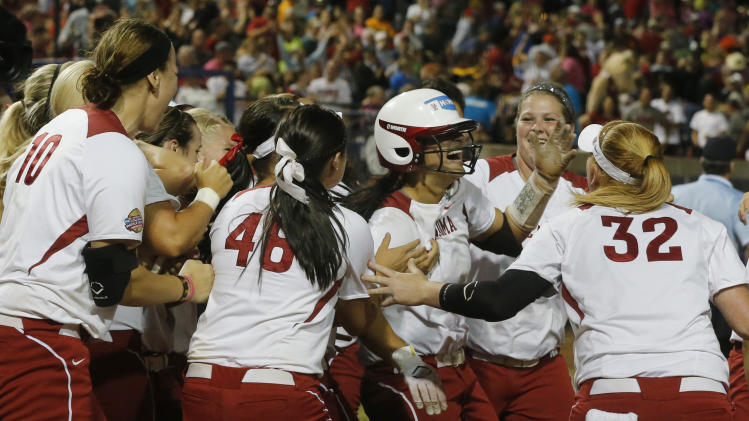 Oklahoma infielder Lauren Chamberlain, in center with batting helmet, is mobbed by her teammates following her 12th inning home run against Tennessee in the first game of the best of three Women's College World Series NCAA softball championship series in Oklahoma City, Monday, June 3, 2013. Oklahoma won 5-3 in 12 innings.(AP Photo/Sue Ogrocki)