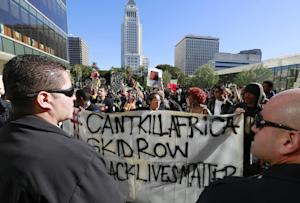 Protestors carry a banner during a rally in front of…