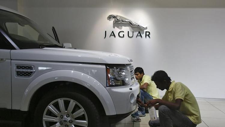 Showroom attendants polish a vehicle under a Jaguar logo at a Jaguar Land Rover showroom in Mumbai