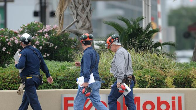 Refinery workers walk at the plant after a fire that injured 12 contact workers, Wednesday, April 17, 2013 in Beaumont, Texas. ExxonMobil Spokeswoman Rachael L. Moore says in a statement that twelve contract workers were hospitalized Wednesday, and six of those hurt Wednesday at the refinery in Beaumont were being transported to hospitals for further treatment. She says their conditions were not immediately known. The fire happened around 10:30 a.m. in a process unit that was down for maintenance at the refinery. All other employees have been accounted for.  (AP Photo/The Enterprise, Guiseppe Barranco)  MANDATORY CREDIT, NO SALES, MAGS OUT, TV OUT