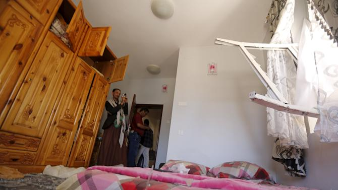 Man takes photos of a room in a house damaged after an air strike hit a nearby army weapons depot in Sanaa