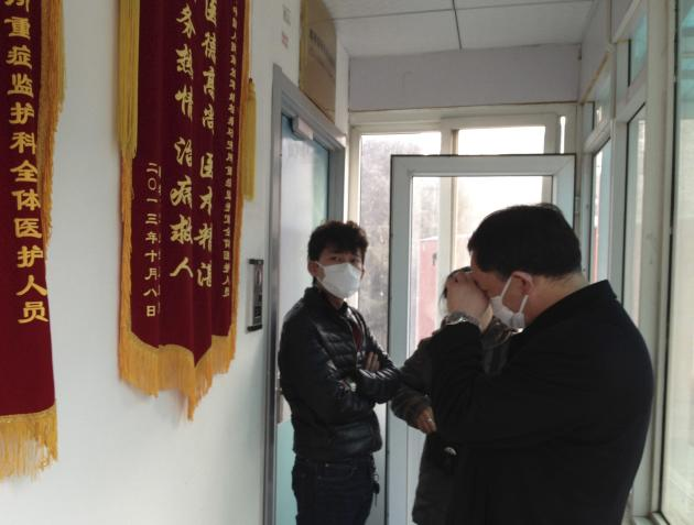 File photo of friends of human right activist Cao standing in front of an intensive care unit where Cao is hospitalized as they are not allowed to go inside of the unit at a hospital in Beijing