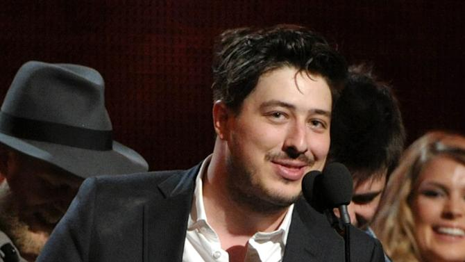 """FILE - This Feb. 10, 2013 file photo shows Marcus Mumford accepting the award on stage for album of the year for """"Babel"""" by Mumford & Sons at the 55th annual Grammy Awards in Los Angeles. Paul McCartney and Mumford & Sons are among the headliners for the 2013 Bonnaroo Music & Arts Festival in Manchester, Tenn. The four-day festival, held on a rural 700-acre farm, will be held June 13-16, 2013. (Photo by John Shearer/Invision/AP, file)"""