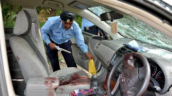 A Pakistani police officer examines the car of prosecutor Chaudhry Zulfikar who was targeted by gunmen in Islamabad, Pakistan on Friday, May 3, 2013. Gunmen killed Pakistan's lead prosecutor investigating the assassination of former prime minister Benazir Bhutto as he drove to court in the capital on Friday, throwing the case that also involves former ruler Pervez Musharraf into disarray. (AP Photo/B.K. Bangash)