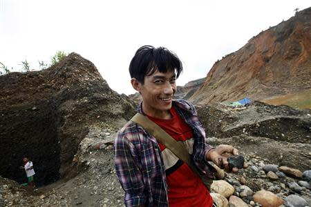 A hand-picker shows the unwashed jade that he just found in a jade mine in Hpakant township, Kachin State