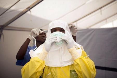 Health workers put on protective gear before entering a quarantine zone at a Red Cross facility in the town of Koidu