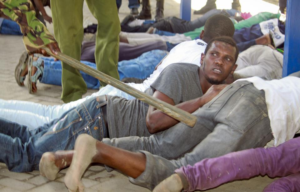 FILE - In this Friday, Oct. 4, 2013 file photo, youths lie on the ground after being arrested by security forces following rioting in reaction to the death of Muslim cleric Sheik Ibrahim Ismael, after Friday Muslim prayers in Mombasa, Kenya. (AP Photo, File)