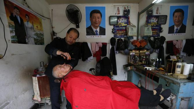 A barber shaves the face of his customer next to posters of Chinese President Xi and his wife Peng, at his barber shop in Yongjia county