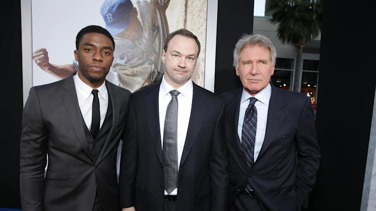 "Chawick Boseman, Producer Thomas Tull and Harrison Ford at The Los Angeles Premiere of Warner Bros. Pictures' and Legendary Pictures' ""42"", on Tuesday, April, 9th, 2013 in Los Angeles. (Photo by Eric Charbonneau/Invision for Warner Bros./AP Images)"