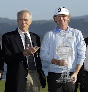 Film great Clint Eastwood, left, gestures toward Brandt Snedeker, right, after presenting him with his trophy on the 18th green of the Pebble Beach Golf Links following the AT&T Pebble Beach Pro-Am golf tournament, Sunday, Feb. 10, 2013, in Pebble Beach, Calif. Snedeker won the tournament after shooting a 7-under 65. (AP Photo/Eric Risberg)