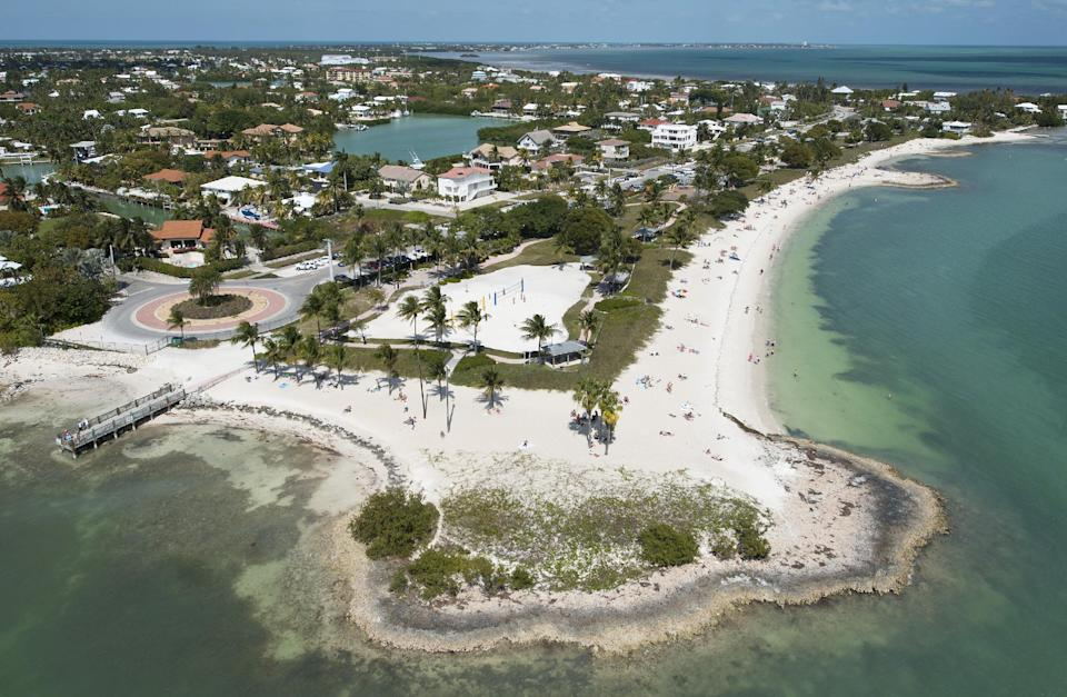 In this Sunday, March 10, 2013, photo provided by the Florida Keys News Bureau, Florida Keys residents and visitors enjoy Sombrero Beach Park in Marathon, Fla. The free-admission park includes volleyball courts, picnic pavilions, playground equipment, restrooms and showers. (AP Photo/Florida Keys News Bureau, Andy Newman)