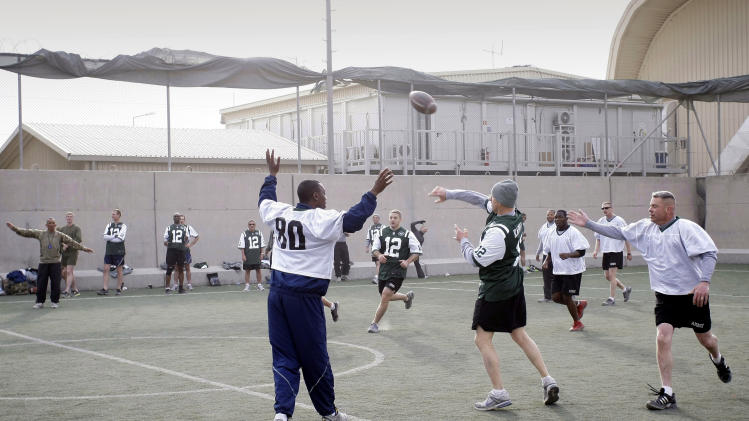 U.S. soldier play football to mark Thanksgiving at the U.S.-led coalition base in Kabul, Afghanistan, Thursday, Nov. 22, 2012. (AP Photo/Musadeq Sadeq)