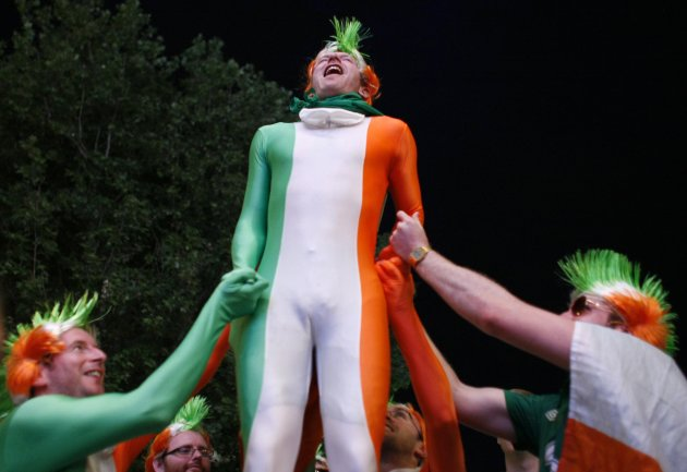 Irish supporters lift a fellow supporter up as they watch the Euro 2012 soccer match between Italy and Ireland at a fan zone in Poznan