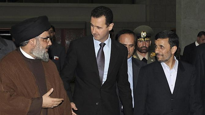 FILE -- In this Thursday February 25, 2010 file photo, released by the Syrian official news agency SANA, Hezbollah leader sheik Hassan Nasrallah, left, speaks with Syrian President Bashar Assad, center, and Iranian President Mahmoud Ahmadinejad, right, upon their arrival for a dinner, in Damascus, Syria. Syria's civil war has morphed into a proxy fight in which Shiite Iran has strongly backed Assad, while Sunni Arab nations have backed rebels. Many Sunni hard-liners around the Mideast have taken Hezbollah's intervention in Syria almost as a declaration of war by Shiites against Sunnis. (AP Photo/SANA, File)