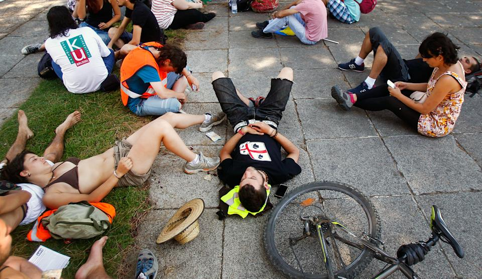 Protesters rest after traveling to Madrid from many parts of Spain to demonstrate against the country's near 25 percent unemployment rate and stinging austerity measures introduced by the government in Madrid, Spain, Saturday, July 21, 2012. (AP Photo/Andres Kudacki)