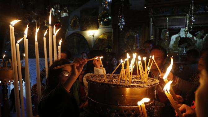 Christian worshipers light candles inside the Church of Nativity, ahead of Christmas in the West Bank city of Bethlehem