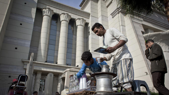 An Egyptian street vendor serves tea for supporters of Egyptian President Mohammed Morsi, unseen, during a protest in front of Egypt's top court, in Cairo, Egypt, Monday, Dec. 3, 2012. The Egyptian president's top legal adviser says the country's election commission has begun preparations for the referendum on Dec. 15 on a highly contentious draft constitution. (AP Photo/Nasser Nasser)