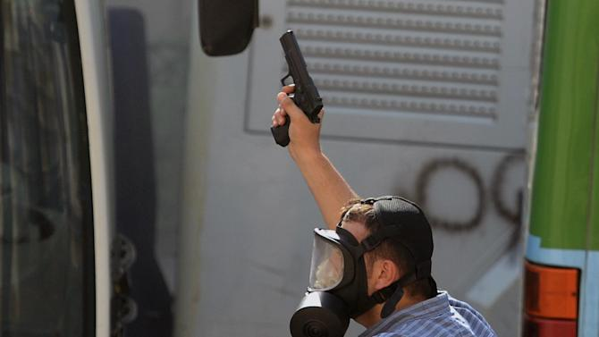 A security officer fires in the air as they  clash with protesters at the city's main Taksim Square in Istanbul, Turkey, Saturday, June 1, 2013. Turkish police retreated from a main Istanbul square Saturday, removing barricades and allowing in thousands of protesters in a move to calm tensions after furious anti-government protests turned the city center into a battlefield. A second day of national protests over a  violent police raid of an anti-development sit-in in Taksim square has revealed the depths of anger against Prime Minister Recep Tayyip Erdogan, who many Turks view as increasingly authoritarian and dismissive of opposing views.(AP Photo)