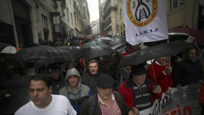 Railway workers march under the rain towards the Portuguese economy ministry during a protest in Lisbon, Thursday, Jan. 17, 2013. The workers were protesting against salary cuts, that is as a part of an austerity economic measures taken by the Portuguese government linked to a euro 78 billion ($102 billion) bailout needed in May 2011. (AP Photo/Francisco Seco)