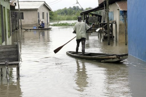 Two men paddle canoes to their homes at Od-Ogun, Ikorodu Road in Lagos on October 6, 2010. Flooding caused by heavy rains in central Nigeria has killed at least 28 people, with many others still missing, while also destroying homes, bridges and farmland, officials said Tuesday.