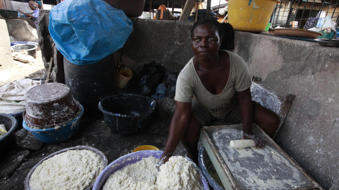 In this photo taken Friday May 3, 2013 a woman produces cassava flour from cassava in a market in Lagos, Nigeria. Scientists say a disease destroying entire crops of cassava has spread out of East Africa into the heart of the continent, is attacking plants as far south as Angola and now threatens to move west into Nigeria, the world's biggest producer of the potato-like root that helps feed 500 million Africans. (AP Photo/Sunday Alamba)
