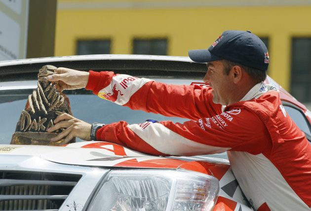 Toyota's driver Giniel De Villiers, from South Africa, places his trophy on his car as he celebrates his third place during the 2012 Argentina-Chile-Peru Dakar Rally award ceremony in Lima, Peru, Sund