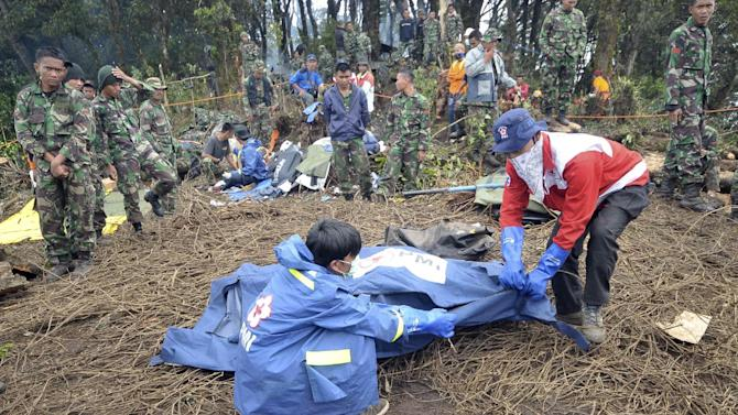 Rescuers prepare a body bag containing the remains of a victim of the crash of Sukhoi Superjet-100 on the peak of Mount Salak, West Java, Indonesia, Tuesday, May 15, 2012. Joint teams of Indonesian and Russian experts continued to comb through debris at the bottom of a 1,500-foot (500-meter) ravine on Tuesday afternoon to find the black box of the new passenger jet with 45 people on board that slammed into a cliff atop the dormant Indonesian volcano last week. (AP Photo/Jefri Tarigan)