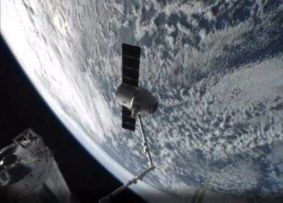 A SpaceX Dragon cargo capsule is seen at the end of the International Space Station's robotic arm, with the bright Earth in the background, in this view from a station camera on March 26, 2013 during undocking activities.